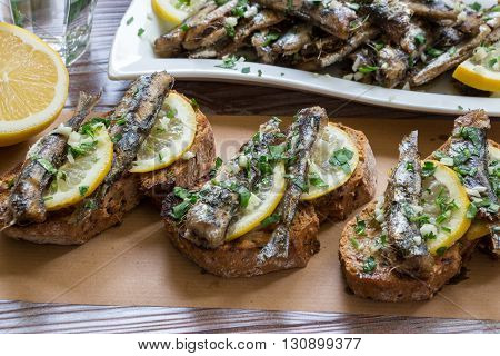 In the foreground sandwiches with fresh sardines, in the background a plate of sardines, a glass of water, parsley, garlic, lemon, olive oil. Snack from sandwiches with sardines. Horizontal. Daylight.
