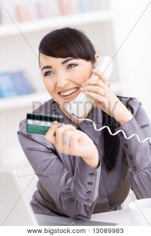 Sorridente jovens mulheres compras on-line em casa, mantendo o cartão de crédito na mão e falar ao telefone.