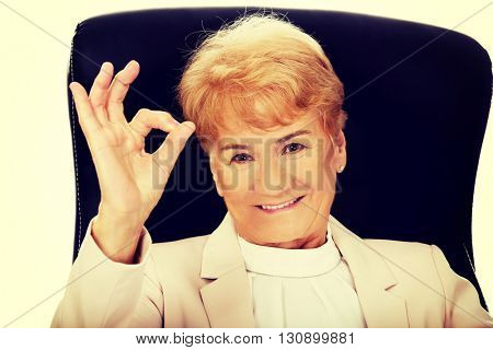 Smile elderly business woman sitting on armchair and show ok sign