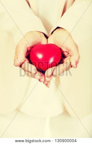 Elderly woman holding heart model on open palms