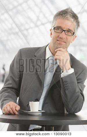 Businessman standing at coffee table in office lobby, leaning on hand, thinking. Isolated on white.