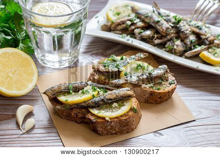 In the foreground sandwiches with fresh sardines, in the background a plate of sardines, a glass of water, parsley, garlic, lemon, olive oil. Snack from sandwiches with sardines. Horizontal. Close.