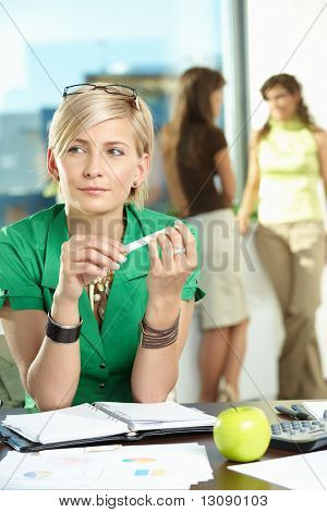 Portrait of young businesswoman sitting at office desk, thinking.