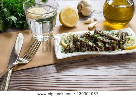 Freshly cooked sardines on a plate near fork and knife, glass of sparkling water, bunch of parsley, half a lemon, garlic, olive oil. Fresh sardines for lunch. Horizontal. Daylight.