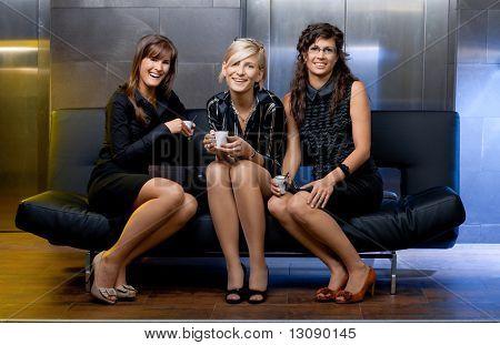 Grupo de mujeres empresarias jóvenes sentados en el sofá en el vestíbulo de la oficina, haning tomar una pausa, sonriendo.
