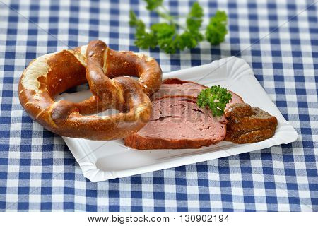 Bavarian takeaway food:  Slices of warm meatloaf with sweet mustard and a pretzel on a paper plate