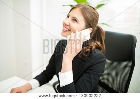 Businesswoman talking on the cellphone while sitting at the desk in her office