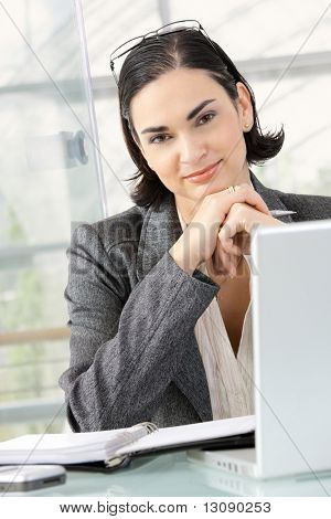 Young businesswoman thinking leaning on hands, sitting at office desk.