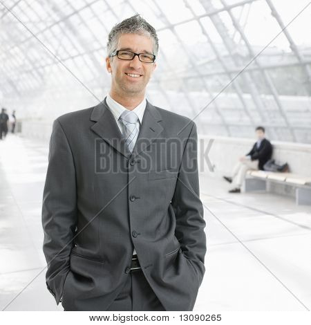 Portrait of happy businessman standing with hands in pocket in office lobby, smiling.