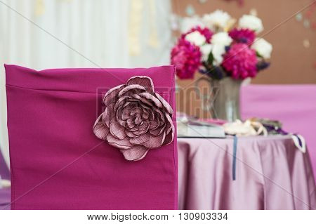 Decor on red chair Marsala with handmade flower for wedding ceremony.