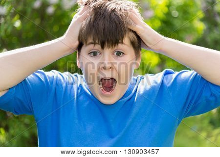 Teen boy screaming and holding his hands behind his head