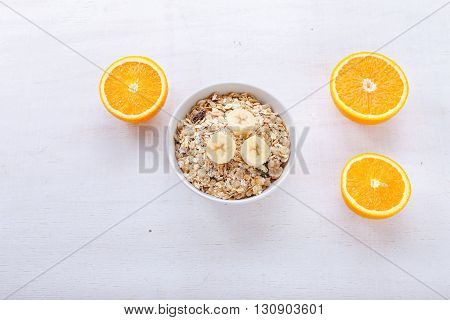 Granola bananas and orange slices on a light wooden surface. Healthy food