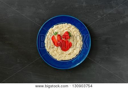 Oatmeal porridge with strawberries in vintage blue plate on a dark surface top view. Healthy breakfast