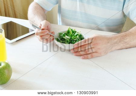 man vegetarian a having a breakfast of salad sitting in the kitchen on white wooden table