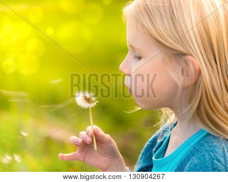 Little blonde girl blowing wishes at a dandelion