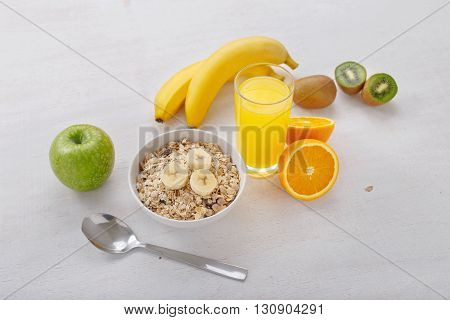 Granola with fruit and orange juice on a light wooden surface. Healthy food