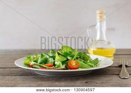 Close up plate of fresh salad with carafe of oil on wooden table. Helpful and simple food