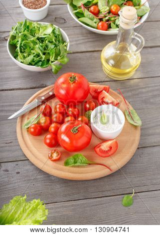 set of tomato on the wooden table with green salad leaves flax seeds and oil top view. Ingredients for the preparation of wholesome food
