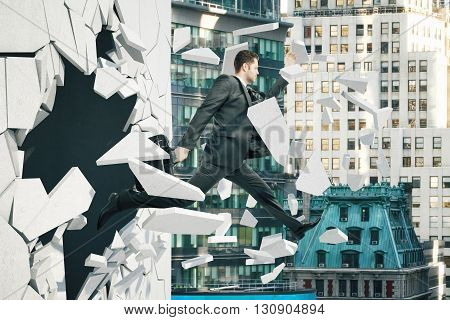 Business breakthrough success concept with businessman jumping through wall on city background
