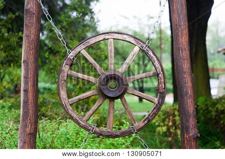 old wooden wheel from a cart in village.