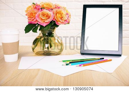 Roses in vase blank picture frame paper sheets with colorful pencils and take away coffee cup on wooden desktop and white brick wall background. Mock up