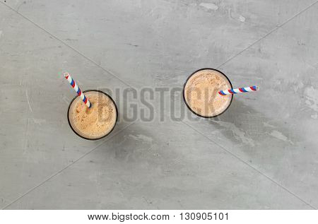 Two chocolate milkshake on a light surface top view