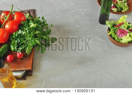 Set of vegetables on white surface with copy space. Branch tomatoes bunch of parsley lettuce radishes and cucumbers. Helpful and diet food.