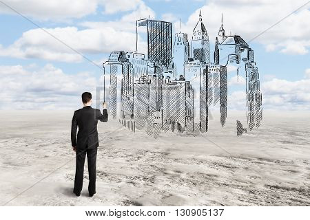 Young architect drawing abstract construction sketch on sky background