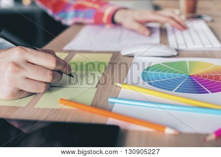 Side view of businessman's hand keyboarding and making notes on stickers placed on wooden desktop with colorful diagram pencils and other items