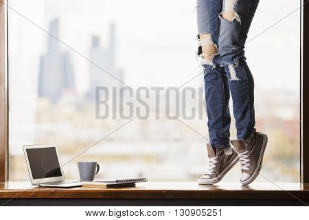 Woman's legs in grey sneakers standing on windowsill with blank laptop screen coffee cup and notepads on blurry city background. Mock up