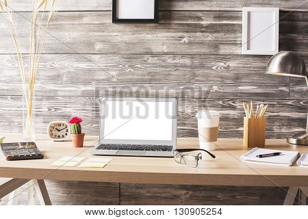 Blank white laptop on wooden designer desktop with coffee stationery items and blank picture frames above. Mock up
