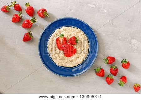 Oatmeal porridge with strawberries on the light surface top view. Healthy breakfast image