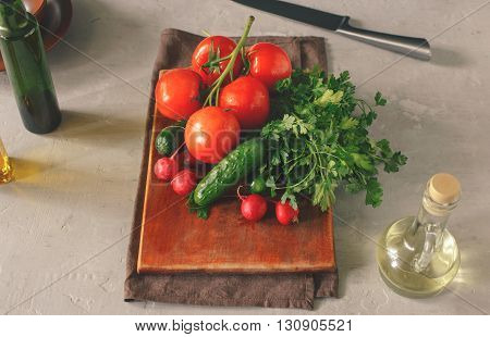 Set of fresh vegetables on white table on a wooden kitchen board top view. Branch tomatoes bunch of parsley radishes and cucumbers. Helpful and diet food
