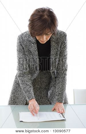 Senior businesswoman showing financial figures on paper, isolated on white background.