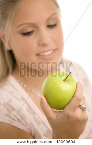 Closeup portrait of beautiful girl holding a green apple, smiling. Selective focus on apple, isolated on white background.