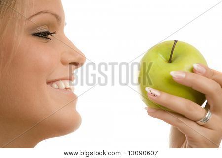 Closeup portrait of beautiful girl holding a green apple, smiling. Side view, isolated on white background.