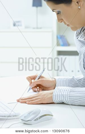 Closeup portrait of young woman writing with pen on paper, focus on hands.
