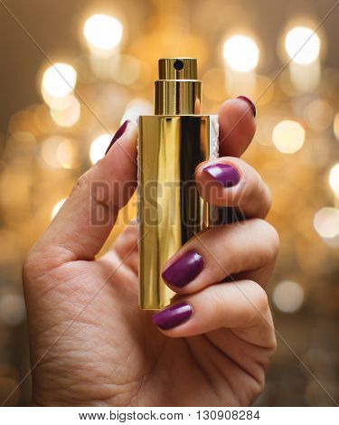 small Gold bottle of perfume in hand