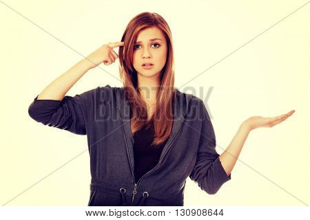 Teenage woman holding something on open palm and thinking about something