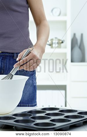 Female hands whipping eggs in bowl, using egg whisk.