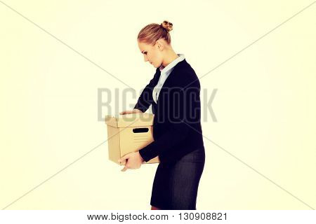 Sad business woman carrying box after loosing job