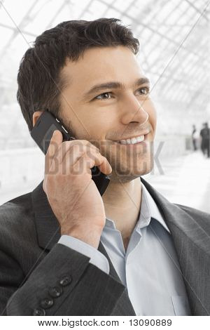 Closeup portrait of happy businessman talking on mobile in office lobby.