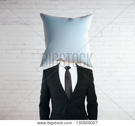 Pillow headed businessman on white brick wall background. Mock up
