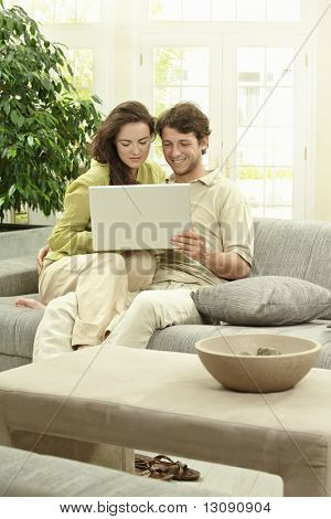 Young couple using laptop computer at home, sitting at couch, smiling.