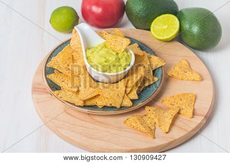 Green Guacamole with nachos and avocado on white wooden background