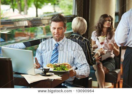 Businessman sitting at table in cafe, eating club sandwich and  using laptop computer. Waiter serving sweets in the background.