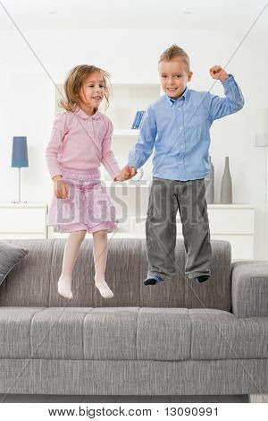 Happy children jumping on couch at home, smiling.