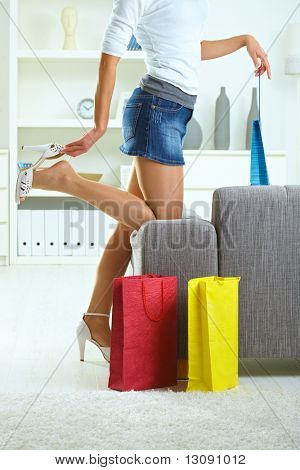 Woman taking off high heel shoe at home, after a day of shopping.