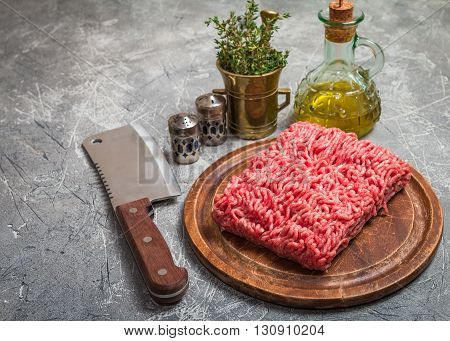 Minced meat on  cutting board with seasoning and fresh thyme on gray background, top view