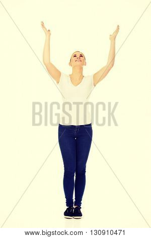 Young woman with outstretched arms looking up